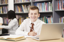 Portrait Of Male High School Student Wearing Uniform Working At Laptop In Library