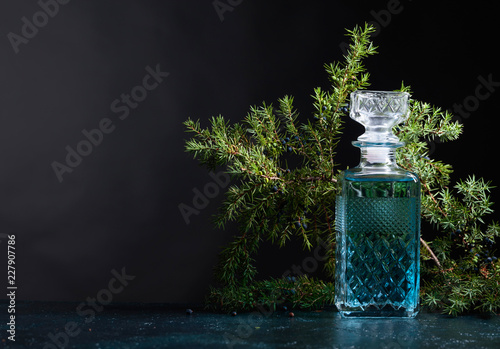 Blue gin in crystal decanter and juniper branch with berries.