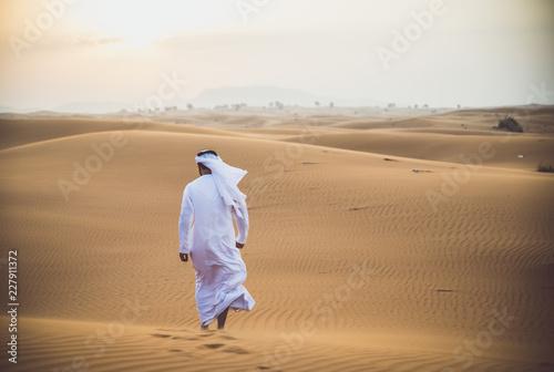 Fototapeta premium Arabski mężczyzna chodzący po pustyni z tradycyjnymi ubraniami emiratów