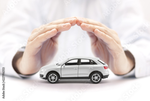 Car insurance. Small silver car covered by hands. Canvas Print