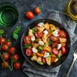 panzanella, traditional italian tomato, mozzarella and bread salad in black bowl