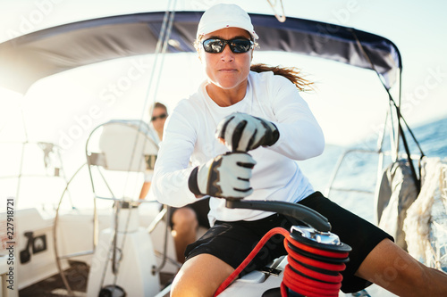 Fototapeta Attractive strong woman sailing with her boat