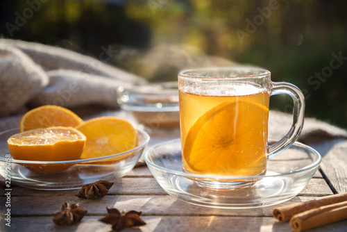 Foto op Plexiglas Thee hot ginger tea with orange slices and spices on a wooden table in the sun, healthy drink against cold, copy space