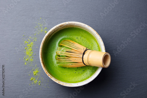 Matcha green tea cooking process in a bowl with bamboo whisk. Black slate background. Top view.