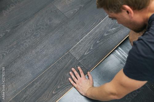 Obraz man installing laminate floor - fototapety do salonu