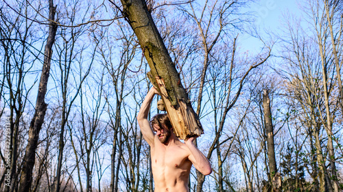 Fényképezés  Man brutal strong attractive guy collecting wood in forest