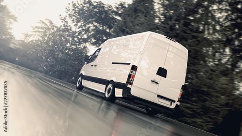 Fotografia Weißer Transporter fährt schnell auf einer nassen Landstraße der Sonne entgegen