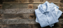 Stack Of Male Folded Shirts On Rustic Background, Top View