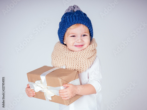 eadde6e6225 Happy little smiling blonde curly hairstyle boy in a knitted blue hat with  christmas gift box ...