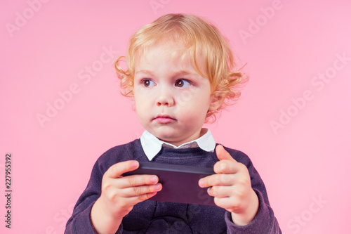little boy blond curls hairstyle in business suit watching somethings interesting cell phone. handsome child fashionable kid on a pink background in the studio