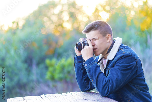 Young man sitting outdoors with his camera