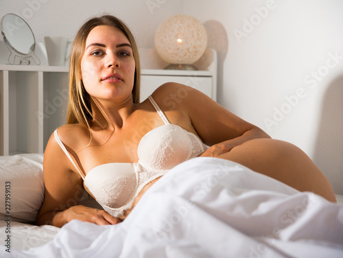 Tuinposter Akt Woman in lingerie lying in bed
