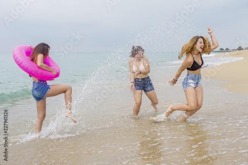 Group of female teenagers walking and enjoying on a beach sand