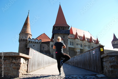 Fototapety, obrazy: A woman in tree position of yoga in front of Corvin Castle, Romania