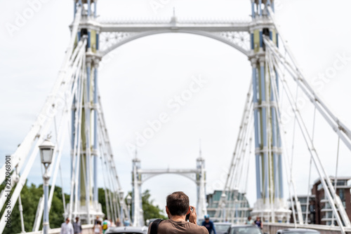 Photo  London, UK back of man tourist taking pictures view of city Albert bridge with c