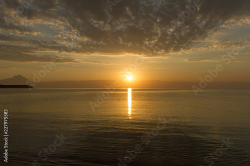Silhouette of mount Athos at sunrise or sunset with light rays and sea panorama in Greece