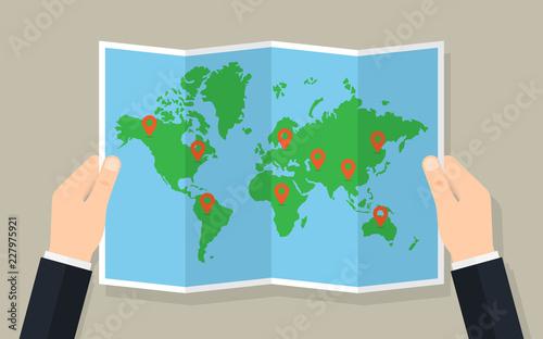 Trzymaj ręce złożone papierową mapę świata ze znacznikami