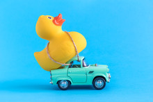 Rubber Duck And Small Car Toys Abstract Isolated On Blue.