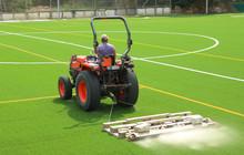 Tractor Preparando El Nuevo Césped Artificial De Un Campo De Fútbol, Poniendo Arena