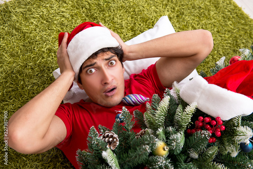 Fotografering  Young man drunk at home after christmas party