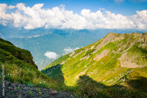 Spoed Foto op Canvas Beige Green land landscape mountains valley in summer afternoon with gentle clouds over peaks