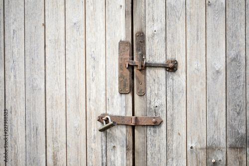 Cerrojo oxidado en puerta de madera