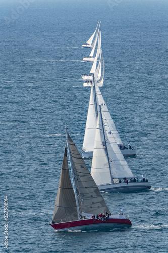 Barche a vela in competizione durante una regata, con vento forte