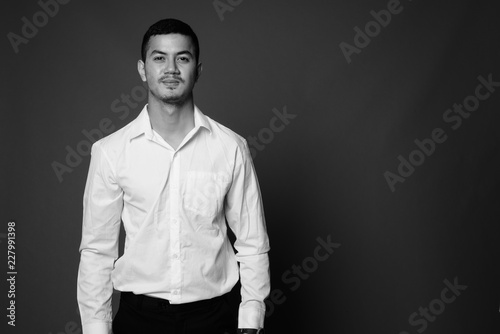 Valokuva  Young multi-ethnic Asian businessman against gray background in