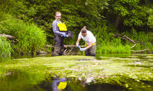 Man And Woman Scientist Environmentalist Standing In A River. Woman Taking Sample Of Water And Pouring It Into The Test Tube. Man Holding Toolbox