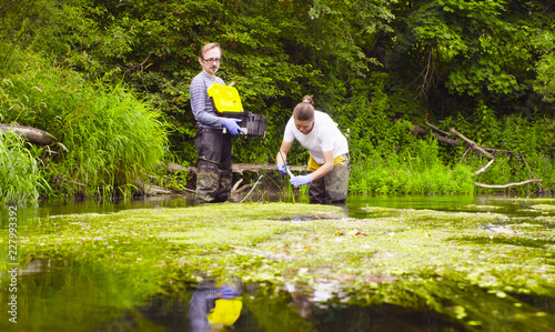 Man and woman scientist environmentalist standing in a river Canvas Print