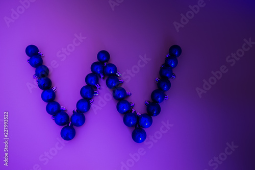Fotografía  Christmas alphabet of blue neon Christmas balls on a gradient lilac background