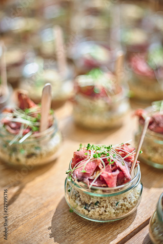 Tasty appetizers with wooden spoons served in glass jars on wooden table Wallpaper Mural