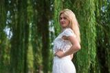 Fototapeta Las - Young blond woman near river, bright summer photo.