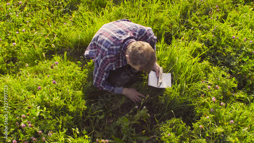 Valokuva  The man scientist ecologist sitting on the meadow and exploring plants
