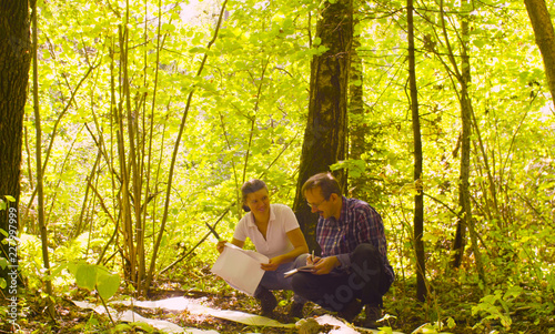 Valokuva  Two ecologist getting samples of soil in the forest inside square marking site