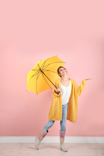 Woman With Yellow Umbrella Near Color Wall