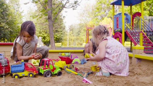 Two girls sitting in a sandbox and playing in the sand Canvas Print