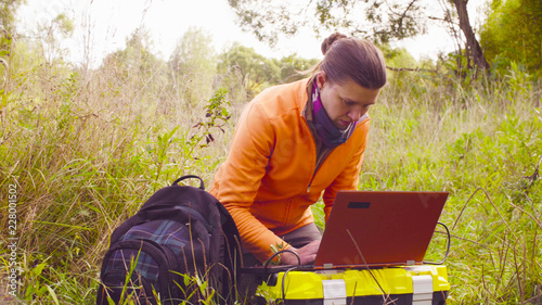 Fototapeta Woman scientist ecologist working on a laptop in the forest