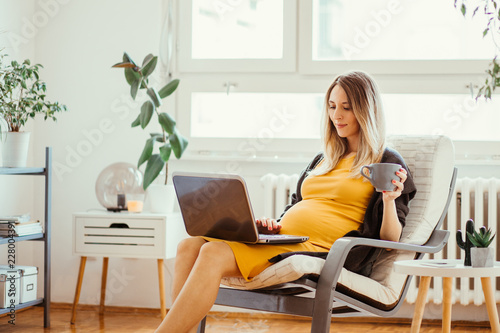 Terrific Pregnant Young Woman Sitting In Rocking Chair And Using Creativecarmelina Interior Chair Design Creativecarmelinacom
