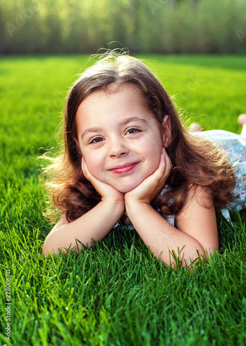 Foto op Canvas Artist KB Portrait of an adorbale child laying on a fresh, green lawn