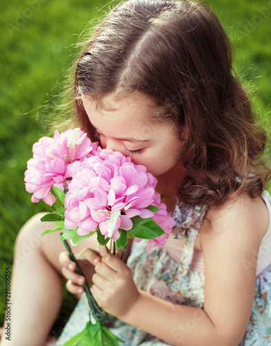 Foto op Canvas Artist KB Pretty cute child holding and sniffing flowers