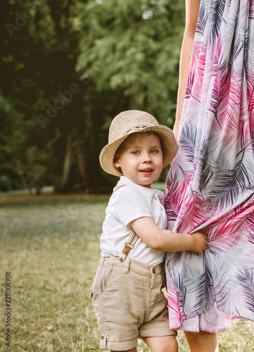 Foto op Canvas Artist KB Cute little boy holding a mother's leg