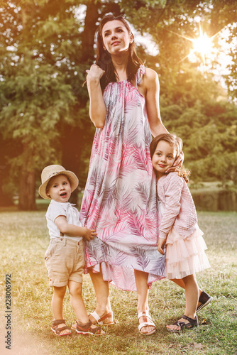 Foto op Canvas Artist KB Adorable, cheerful kids holding their mother's legs