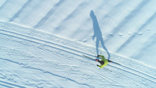 AERIAL: Flying Above Woman Cross Country Skiing Across Large Snow Covered Plain.