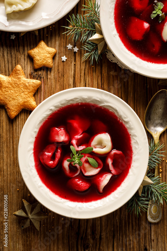 Christmas beetroot soup, borscht with small dumplings with mushroom filling in a ceramic bowl on a wooden table.  Traditional Christmas eve dish in Poland.