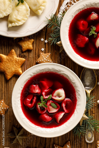 Christmas beetroot soup, borscht with small dumplings with mushroom filling in a ceramic bowl on a wooden table, top view.  Traditional Christmas eve dish in Poland.
