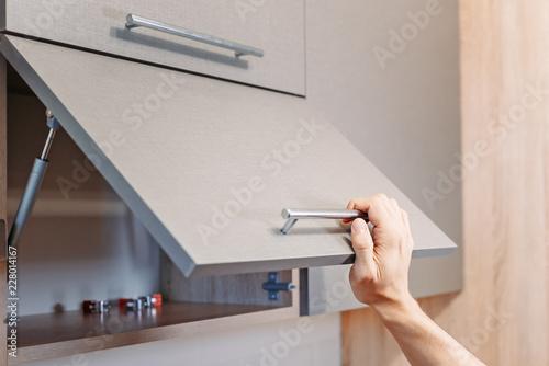 man hand open kitchen cupboard with handle Wallpaper Mural