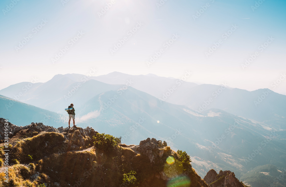 Fototapety, obrazy: Mountain hiker with backpack tiny figurine stay on mountain peak with beautiful panorama
