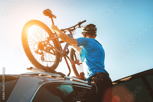 Mountain biker man take of his bike fron the car roof