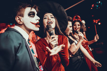 Young People In Halloween Costumes Singing Karaoke
